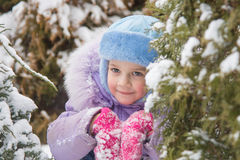 Joyful five years girl hiding in the snow-covered fur-trees Stock Images