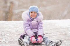 Joyful five years girl rolls down from the icy hill. Five-year girl riding winter on a snowy hill surrounded by other children Royalty Free Stock Photo