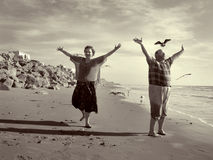 The Joyful Freedom Of Retirement. Part of my sepia toned retired couple on the beach series. Keyword series1rc to see the entire series with background and Royalty Free Stock Photo