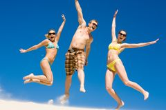 Joyful friends. Portrait of leaping teenagers on the beach wearing sunglasses and laughing stock photos