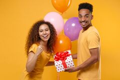 Joyful friends couple african american guy girl isolated on yellow background. Birthday holiday party concept. Celebrate