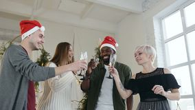 Joyful friends drinking toast while celebrating Christmas Eve or New Year , celebration lovely occasion in christmas. Decorated apartment or office. Concept of stock footage