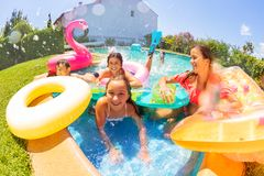 Joyful friends playing in outdoor swimming pool royalty free stock images