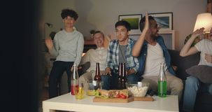 Joyful friends playing video game celebrating victory at night in apartment. Joyful friends multiracial group are playing video game celebrating victory at night stock footage