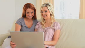 Joyful friends sitting on a couch with a laptop stock video footage
