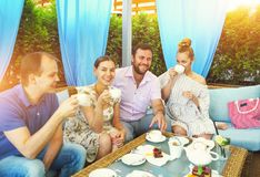 Joyful friends sitting by served table in cafe. Outdoors royalty free stock photo