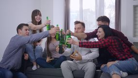 Joyful friends sitting on sofa in front of the TV eating pizza and making toast with beer bottles at home party stock footage