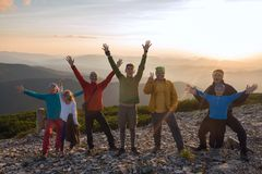 Joyful friends during a travel in mountains. Happy friends during a travel in mountains, stand on the top at sunset and having fun. Amazing adventure in a Stock Photography