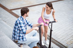Joyful friends using scooters. Involved in jubilation. Positive smiling friends using scooters and resting while having fun royalty free stock photos