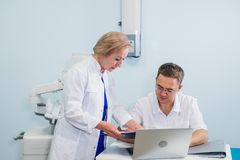 Joyful general practitioners discussing their work at hospital office Stock Image
