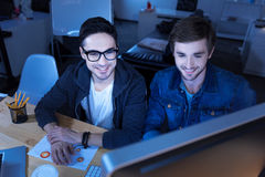Joyful genius hackers hacking into a government website. State security service. Joyful genius handsome hackers hacking into the government website and stealing Royalty Free Stock Photos