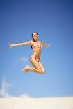 Joyful girl. Portrait of joyful girl leaping on sandy beach during summer vacation and laughing Stock Photo