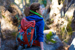 Joyful Girl with Backpack and Hippie style clothing sitting in Forest Royalty Free Stock Photos