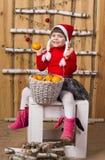 Joyful girl with basket of tangerines Stock Images