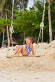 Joyful girl in a bathing suit on a swing. Girl with two braids in a swimsuit sits on a swing on the beach Royalty Free Stock Image