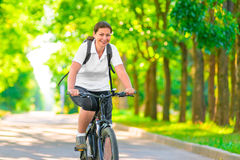 Joyful girl on a bicycle. With a backpack Royalty Free Stock Photography