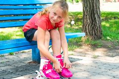 Joyful girl, blond clothes rollers of red color and looks at the camera and smiles, sitting in the park on a blue bench. royalty free stock images