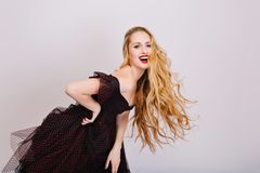 Joyful girl with blonde beautiful long curly hair, model posing at studio with white background, having fun, smiling royalty free stock images