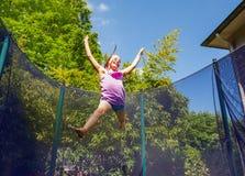 Joyful girl bouncing around a trampoline outdoors stock photography