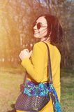 A joyful girl in a bright yellow sweater walks through the spring forest royalty free stock image