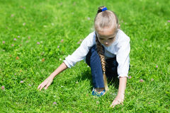 Joyful girl catches in the grass grasshopper Royalty Free Stock Image