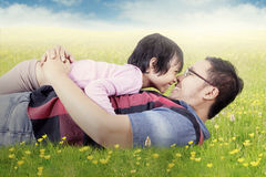 Joyful girl and dad kissing nose on meadow Stock Photos