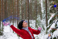 Joyful girl decorates a firtree Royalty Free Stock Photos