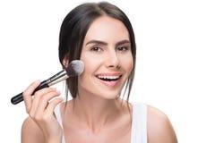 Joyful girl doing facial make-up by brush stock photography