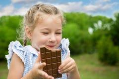 Joyful girl eating chocolate. In the park Royalty Free Stock Image
