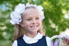 Joyful girl first grader with flowers Royalty Free Stock Image