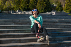 Joyful girl in a funny sunglasses expressively laughs after roll. Joyful girl in a funny sunglasses sits on the steps in the city park, expressively laughs and Royalty Free Stock Photography