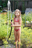 Joyful girl with garden hose and water Royalty Free Stock Photos