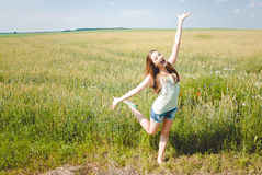 Joyful girl in green field with open arms dancing Stock Photos