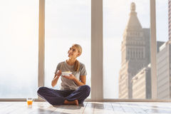 Joyful girl having breakfast at home. Happy young woman is eating cereals in morning. She is looking up with curiosity and smiling. Lady is sitting near window Stock Photo