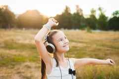 Joyful girl listening music and dancing in the field Stock Image