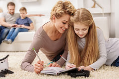Joyful girl having fun with her mother at home stock photography