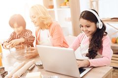 Joyful girl in headphones sits behind laptop next to her grandmother and brother watching tablet in kitchen. Stock Photos