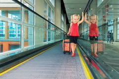Joyful girl with her trunk on airport moving walkway Stock Photo