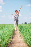 Joyful girl. Jumping high while walking through field Royalty Free Stock Photo