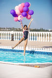 Joyful girl jumping into the pool while holding a bunch of balloons. Stock Photo