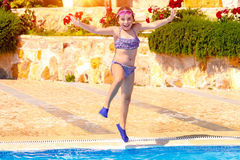 Joyful girl jumping to the pool Royalty Free Stock Photo