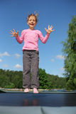Joyful girl jumps on trampoline. Joyful girl dressed in pink T-shirt jumps on trampoline at sunny summer day Stock Photo
