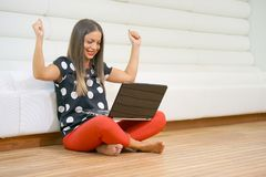 Joyful girl with a laptop on the floor royalty free stock photography
