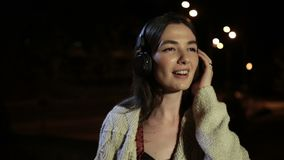 Joyful girl listening music with earphones at night stock footage