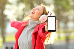 Joyful girl listening music and showing phone screen in winter. Joyful girl listening music and dancing with headphones showing a blank phone screen wearing a stock photos