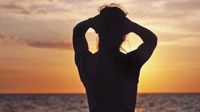 Joyful girl with long hair standing with arms wide spread enjoying the sunset on the beach. slow motion. 1920x1080. Seductive girl with long hair standing with stock video footage