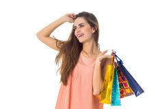 Joyful girl looks away and keeps the color packages from stores isolated on white background Stock Images