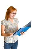 Joyful girl looks in blue folder Royalty Free Stock Photo