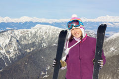 Joyful girl in mountains skiing. Happy attractive young girl holding skis with picturesque winter mountainous background Royalty Free Stock Images