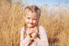 Joyful girl on nature with a blade of grass in hands Royalty Free Stock Photos